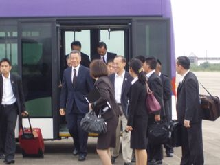 Minister alighting from airport bus with PM