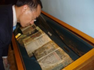 Minister Looking at the Oldest Book Printed in Russia