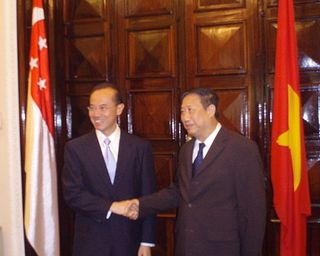 Minister shaking hands with DPM Khiem