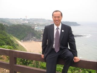 Minister sitting on the barricade on the cliff at Shilla Jeju