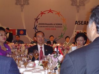 Minister at dinner table with President and Mrs Lee in background