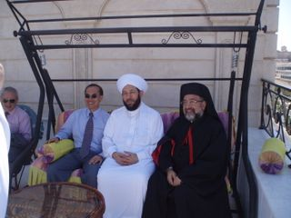 Minister with Sheikh Ahmad and the Arch-Bishop on a swing