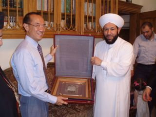 Sheikh Ahmad presenting a verse from the Koran to Minister